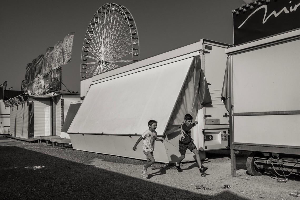 Deux enfants courent dans une fête foraine déserte.